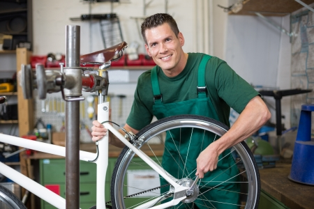 Mechanic or serviceman installing wheel on a bicycle in workshop photo