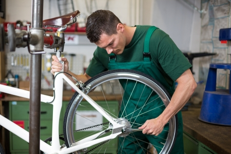 bicycle wheel: Mechanic or serviceman installing wheel on a bicycle in workshop