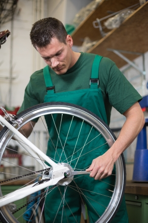 serviceman: Mechanic or serviceman installing wheel on a bicycle in workshop