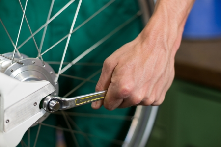 repairer: Closeup of bicycle mechanic with a wrench repairing bike wheel