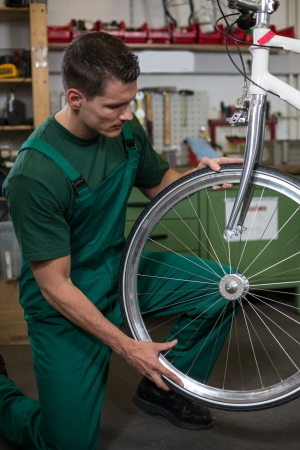 Bicycle mechanic repairing tyre or wheel on bike in a workshop photo