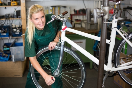 repairer: Bicycle mechanic repairing tyre or wheel on bike in a workshop Stock Photo