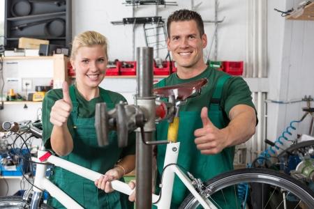 Fahrrad-Mechaniker und Lehrling Reparatur ein Fahrrad in der Werkstatt Standard-Bild - 20596585