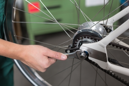 Closeup of bicycle mechanic repairing a bike in workshop Standard-Bild