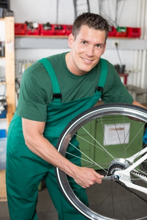 Bicycle mechanic with wrench changing wheel on bike in workshop photo