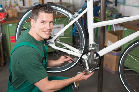 Bicycle mechanic repairing bike in a workshop photo