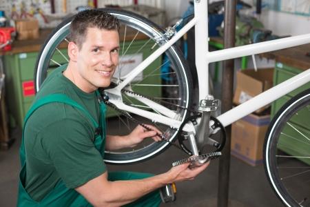 Bicycle mechanic repairing bike in a workshop