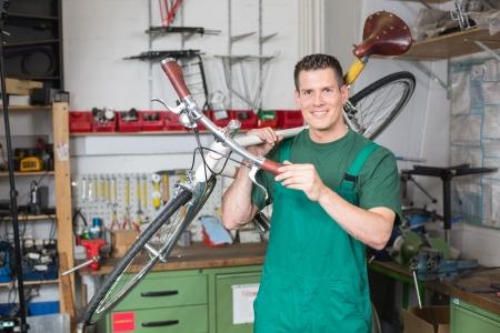 riparatore: Meccanico di biciclette che trasportano una moto in officina sorridente nella fotocamera