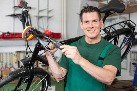 Bicycle mechanic carrying a bike in workshop smiling into the camera photo