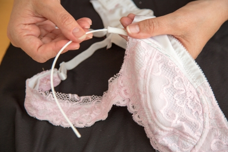 rubber lining: Woman sewing ribbon and rose to lingerie or bra