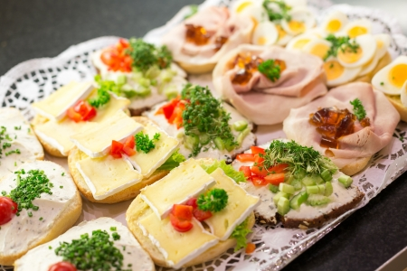Sandwiches on plate at a buffet with cold meat, eggs and cheese