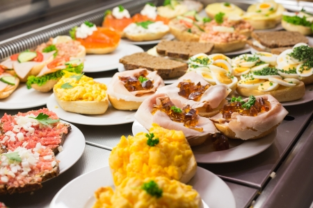 sandwiches: Sandwiches from catering service on plate at a buffet with cold meat, eggs and cheese