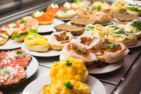 Sandwiches von Catering-Service auf dem Teller zu einem Buffet mit Wurst, Eiern und Käse