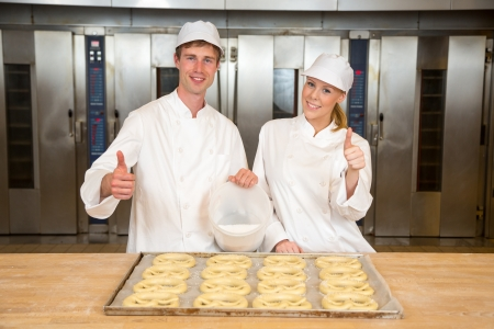 griddle: Bakers in bakery with baking tray full of pretzels giving thumbs up Stock Photo