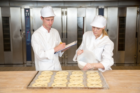 baking tray: Instructor in bakery teaches baker apprentice how to make pretzels Stock Photo