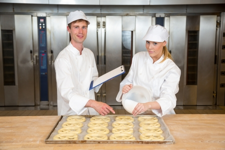griddle: Instructor in bakery teaches baker apprentice how to make pretzels Stock Photo