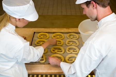 Twee bakkers in de bakkerij of bakhuis bakken pretzels
