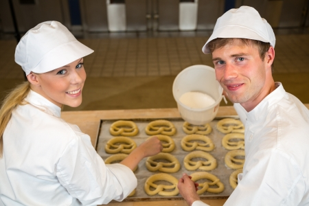 bakery products: Two bakers in bakery or bakehouse baking pretzels