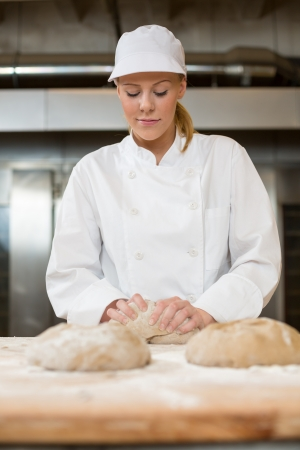 Baker in bakery smiling while kneading dough for bread photo