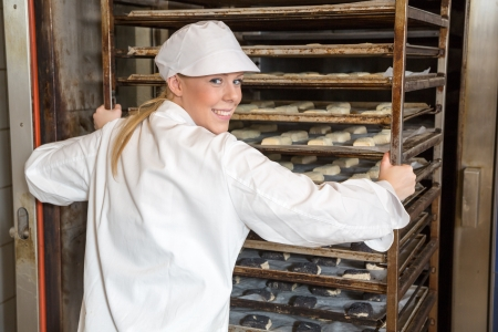 bakery oven: Baker in bakery or bakehouse putting rack with bread, baguettes and buns into the oven