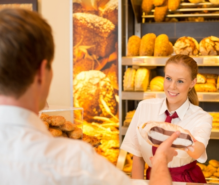 Shopkeeper in bakery or bakers shop selling bag full of bread to customer Standard-Bild