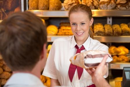 Saleswoman or shopkeeper in bakery handing over a bag full of bread to customer photo