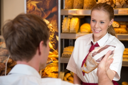 bakery products: Shopkeeper in bakery or bakers shop selling bag full of bread to customer Stock Photo