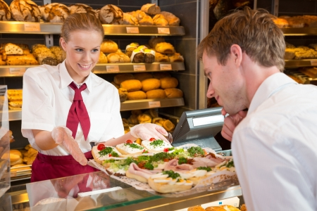 saleswomen: Shopkeeper in bakery or bakers shop presenting tray with sandwiches, cold cut, cheese, cold meat and egg.