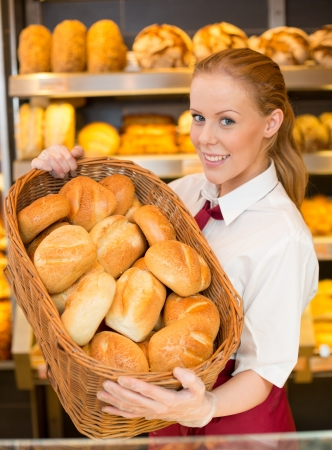 Baker or shopkeeper holding a breadbasket to show bread and buns to customer photo