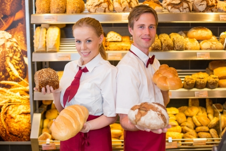 bakery shop: Two bakers or shopkeepers in a bakery presenting different types of bread Stock Photo
