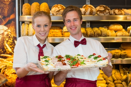 Two shopkeepers or bakers presenting plate with sandwiches at the counter of a bakery to customer photo