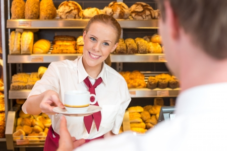 Shopkeeper in bakery or cafe giving cup of coffee or tea to customer
