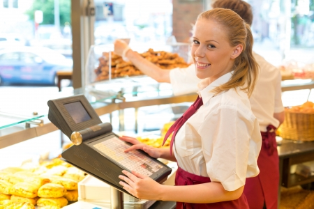 Cashier in a bakery posing with cash register photo