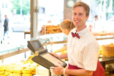 Männlich Kassiererin in einer Bäckerei posiert mit Registrierkasse