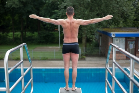 Public Swimming Pools With Diving Boards man standing on diving board at public swimming pool ready to