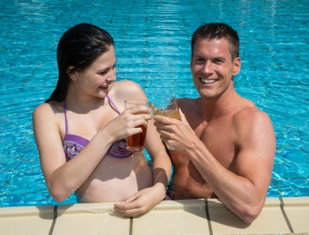 Couple drinking something in the sun at public swimming pool Stock Photo - 21832230
