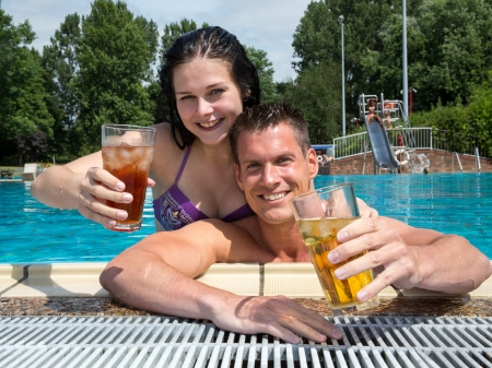 Couple drinking something in the sun at public swimming pool Stock Photo - 21875776