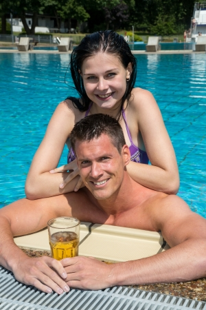 Couple enjoying drinks in their holidays at swimming pool Stock Photo - 21875777