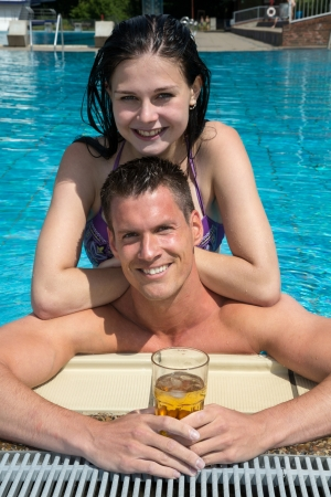 Couple drinking something in the sun at public swimming pool Stock Photo - 21875778