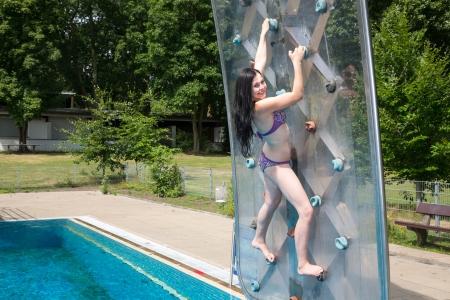 climbing  wall: Woman in Bikini on climbing wall at public swimming pool