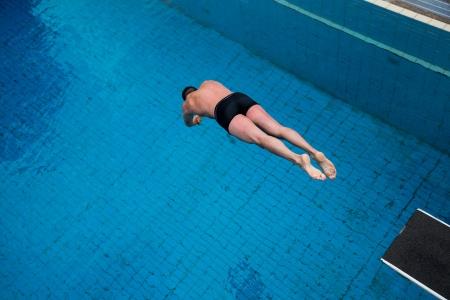 nadar: Hombre saltando de trampolín en la piscina pública