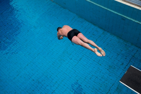 jump suit: Man jumping from diving board at public swimming pool Stock Photo