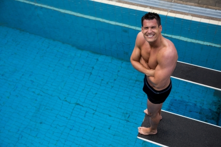 Man on spring board at public swimming pool smiling into camera photo