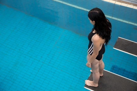 Woman on diving board at public swimming pool being afraid to jump