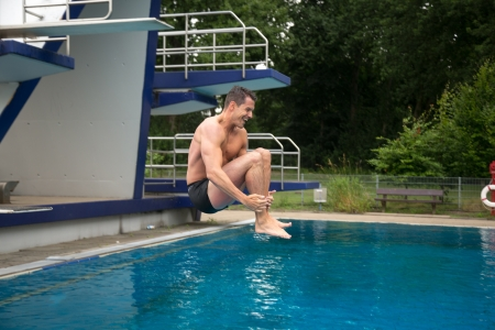 Man at public swimming pool enjoys jumping into the water from diving board photo