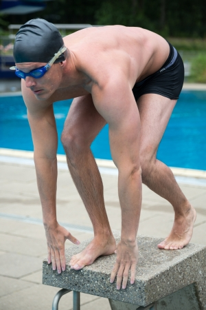 Swimmer on starting block at public swimming pool photo