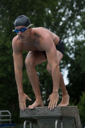 Man standing on starting block at public swimming pool ready to jump photo