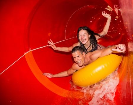 tobogan agua: Pares que animan mientras se divierten desliz�ndose por un tobog�n en la piscina p�blica