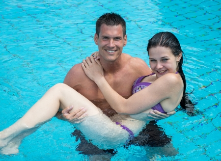 Man carrying his girlfriend in the water at public swimming pool photo