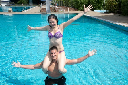 Man and woman posing in the water at public swimming pool  She is sitting on his shoulder
